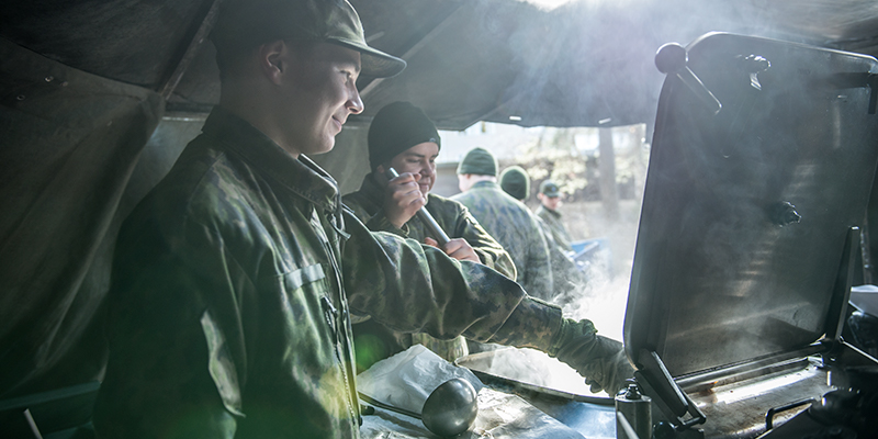 Soldiers preparing a meal with a field kitchen